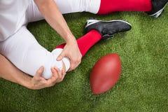 Giocatore di football americano con la lesione in gamba immagini stock libere da diritti