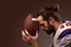 Giocatore di football americano con una palla sul momento da pregare prima del gioco immagini stock