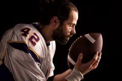 Giocatore di football americano con una palla sul momento da pregare prima del gioco fotografie stock libere da diritti