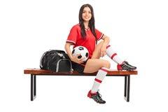 Giocatore di football americano femminile che si siede su un banco fotografia stock