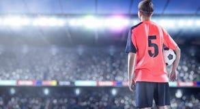 Giocatore di football americano femminile in uniforme di rosso sul campo di calcio immagini stock