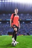 Giocatore di football americano femminile in uniforme di rosso sul campo di calcio fotografia stock