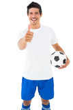 Giocatore di football americano nella palla bianca della tenuta che mostra i pollici su Fotografia Stock Libera da Diritti