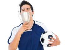 Giocatore di football americano nella tazza e nella palla blu dei vincitori della tenuta fotografie stock