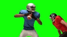 Giocatore di football americano serio che affronta per la palla video d archivio
