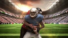Giocatore di football americano serio che affronta per la palla archivi video