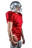Giocatore di football americano serio in jersey rosso che distoglie lo sguardo mentre tenendo palla Immagine Stock Libera da Diritti