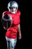 Giocatore di football americano sicuro che mostra palla fotografia stock libera da diritti