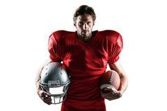 Giocatore di football americano sicuro nel casco e nella palla rossi della tenuta del jersey fotografie stock