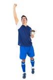 Giocatore di football americano in tazza blu dei vincitori della tenuta immagini stock libere da diritti