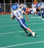 Giocatore di football americano teenager della gioventù che funziona con la sfera Immagini Stock