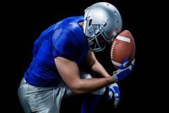 Giocatore di football americano turbato con la palla immagine stock