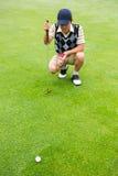 Giocatore di golf accovacciantesi che esamina la palla Fotografia Stock