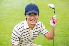 Giocatore di golf accovacciantesi che sorride alla macchina fotografica ed a tenere club Immagine Stock