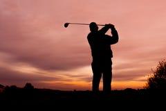 Giocatore di golf al tramonto che colloca sul tee fuori Fotografia Stock