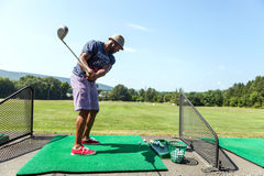 Giocatore di golf alla gamma Immagine Stock