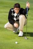 Giocatore di golf che allinea putt Fotografie Stock Libere da Diritti