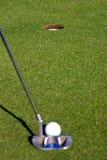 Giocatore di golf che allinea un breve putt - metta a fuoco sul foro Immagini Stock Libere da Diritti