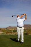 Giocatore di golf che colpisce suo azionamento Fotografia Stock