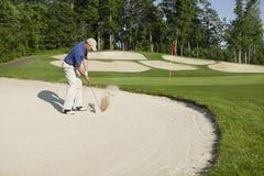 Giocatore di golf che fa saltare dal bunker su verde Fotografia Stock Libera da Diritti