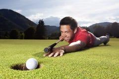 Giocatore di golf che gioca biliardo su verde. Fotografie Stock