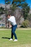 Giocatore di golf che gioca un colpo sul tratto navigabile Fotografia Stock