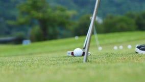 Giocatore di golf che mette palla nel foro, soltanto nei piedi e nel ferro da vedere Fotografia Stock