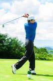 Giocatore di golf che oscilla il suo ingranaggio e colpito la palla da golf Fotografia Stock