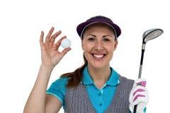 Giocatore di golf che posa con un club di golf e una palla da golf Fotografie Stock