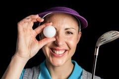 Giocatore di golf che posa con un club di golf e una palla da golf Immagine Stock