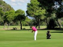 Giocatore di golf che scheggia sul verde Fotografia Stock