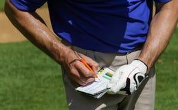 Giocatore di golf che tiene punteggio sui segnapunti fotografia stock libera da diritti