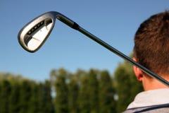 Giocatore di golf che tiene un club di golf nel campo da golf Immagine Stock