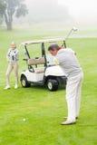 Giocatore di golf circa da collocare sul tee fuori con il partner dietro lui Fotografie Stock