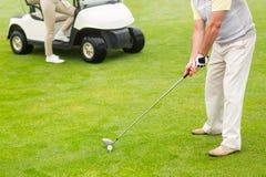Giocatore di golf circa da collocare sul tee fuori con il partner dietro lui Immagini Stock Libere da Diritti