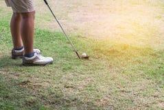 Giocatore di golf con il club di golf del metallo che prepara guidare la palla da golf sul tratto navigabile Fotografie Stock Libere da Diritti