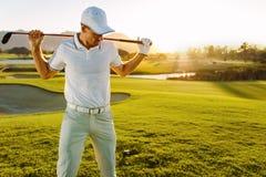Giocatore di golf con il club di golf al corso un giorno di estate Immagine Stock
