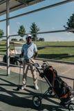 Giocatore di golf con il club di golf a disposizione che sta la borsa di golf vicina Immagini Stock Libere da Diritti