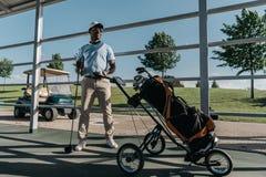 Giocatore di golf con il club di golf a disposizione che sta la borsa di golf vicina con attrezzatura Fotografia Stock