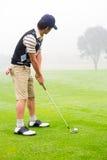Giocatore di golf del concentrato che allinea il suo colpo Fotografia Stock