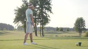 Giocatore di golf del Medio-Oriente bello del ritratto riuscito che oscilla e che colpisce palla da golf sul bello corso Uomo sic video d archivio