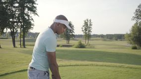 Giocatore di golf del Medio-Oriente bello del ritratto riuscito che oscilla e che colpisce palla da golf sul bello corso Uomo sic stock footage