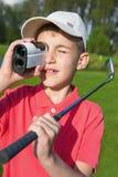 Giocatore di golf del ragazzo che guarda nel telemetro Fotografia Stock