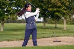 Giocatore di golf della donna che gioca da un bunker della sabbia fotografia stock libera da diritti