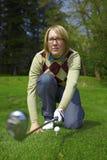 Giocatore di golf della donna che mira con il ferro Fotografie Stock Libere da Diritti