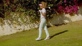 Giocatore di golf della donna che posa davanti alla buganvillea video d archivio