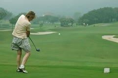 Giocatore di golf della donna che spinge il T immagini stock