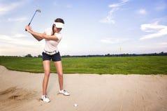 Giocatore di golf della donna nel separatore di sabbia che prepara colpire sfera. Fotografia Stock Libera da Diritti