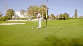 Giocatore di golf della giovane donna che mette per il foro video d archivio