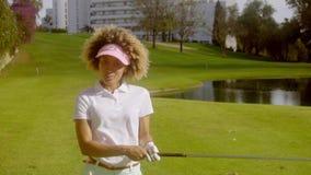 Giocatore di golf della giovane donna davanti ad un lago su un corso archivi video